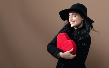 Young woman holding a big heart gift box on a brown background