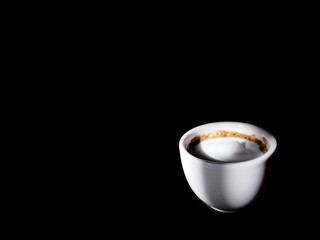 A white cup of cappuccino on black background. Selective focus