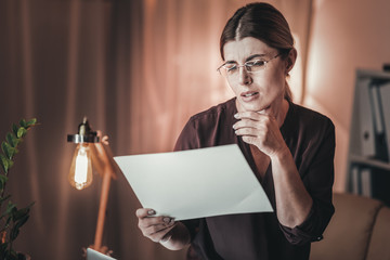Disturbed female freelancer scrutinizing documents