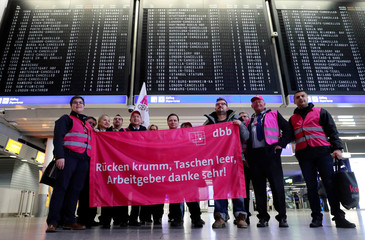Union members with a banner pose for a picture during a strike over higher wages at Germany's largest airport in Frankfurt
