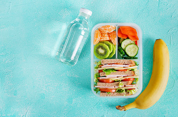 Wall Murals Assortment School lunch box with sandwich, vegetables, water, and fruits on table. Healthy eating habits concept. Flat lay. Top view