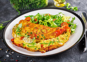 Breakfast. Omelette with tomatoes, avocado, blue cheese and green peas on white plate.  Frittata - italian omelet.