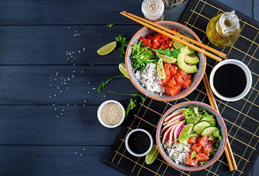 Hawaiian salmon fish poke bowl with rice, avocado, paprika, cucumber, radish, sesame seeds and lime. Buddha bowl. Diet food. Top view
