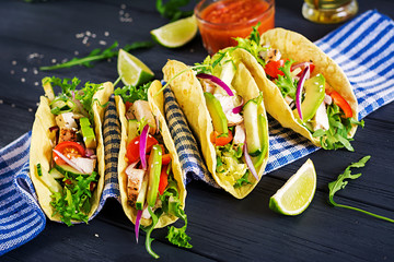 Mexican tacos with chicken meat, avocado, tomato, cucumber and red onion. Healthy tortilla. Wrap food. Taco