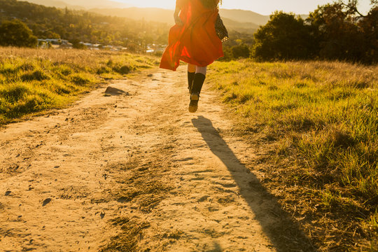 Tan mixed race woman wearing red dress runs away from viewer into sunset