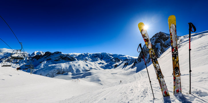 Ski in winter season, mountains and ski touring equipments on the top in sunny day in France, Alps above the clouds.