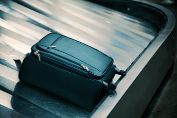 Suitcase on luggage conveyor belt at baggage claim area at airport terminal