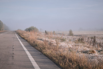 the road goes into the distance into the fog.  Rime on grass