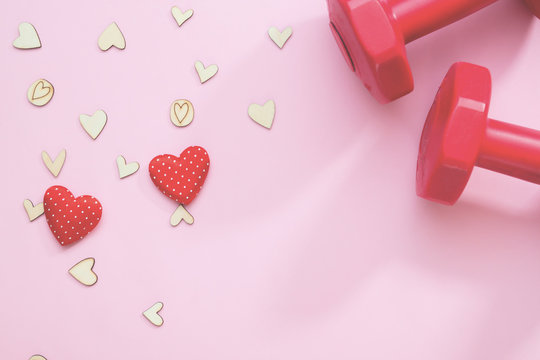 Creative flat lay of health or insurance concept. Hearts and fitness equipment on pink background