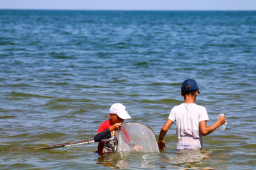 two boys fish with a net in the sea