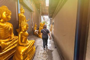 Woman was walking through golden buddha road in Bangkok Thailand.
