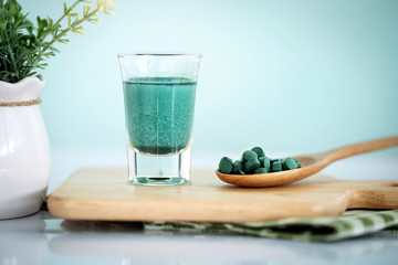 Close up a vegan blue spirulina smoothie and spirulina pills , a healthy superfood diet and detox nutrition concept