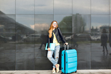 Pretty girl with long hair is standing with suitcase outside on black background. She wears black jacket with jeans and holds laptop. She is dreaming.