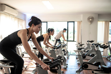 Young beautiful woman and man  exercising  by riding a bicycle in a gym and sweating - Image