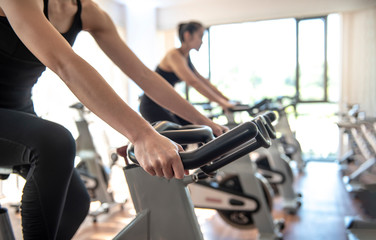 select focus of hand ,burry background Attractive young woman working out on exercise bike at the gym. - Image