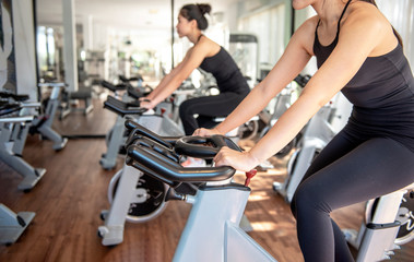 Close up of Attractive young woman working out on exercise bike at the gym. - Image