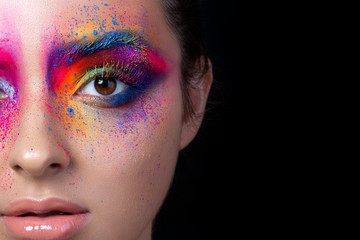 Close up view of female face with bright multicolored fashion makeup. Holi indian color festival inspired. Studio macro shot. Copy space.