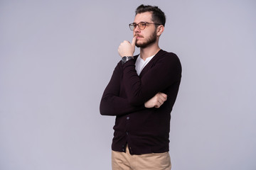 Young handsome man thinking over gray background.