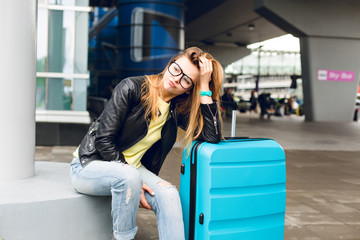 Portrait of pretty girl with long hair in glasses sitting outside in airport. She wears yellow sweater with black jacket and jeans. She leaned to the suitcase and is bored at waiting.