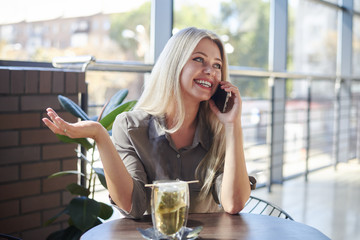 Woman talking on mobile phone at cafe