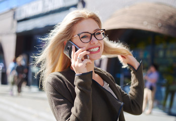 Happy woman talking on mobile phone in city