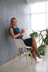 Beautiful businesswoman with file on office chair