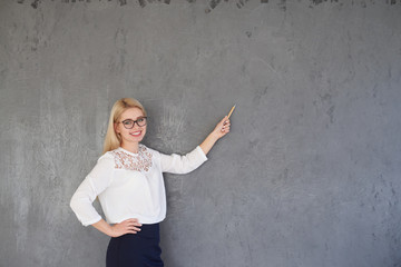 Businesswoman pointing on gray background