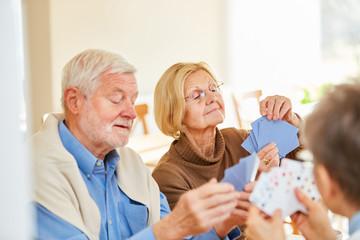 Senioren Paar und Freunde spielen Karten