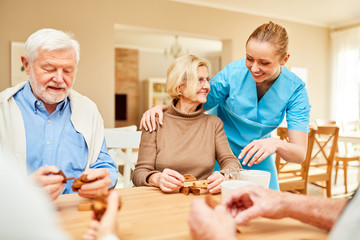 Demente Senioren beim Holzpuzzle Geduldspiel