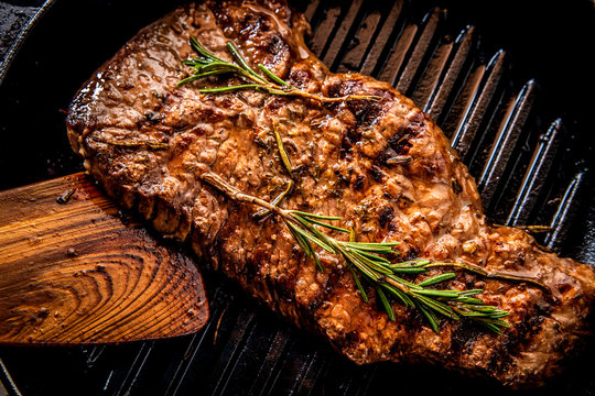 Juicy beef steak with rosemary on a grill pan.