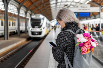 Blonde attractive woman with bouquet of flowers in grey backpack is holding smartphone and waiting train. Photo from the back. Tourism concept