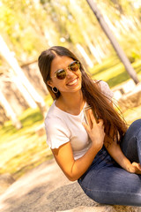 A beautiful smiling young woman in a white shirt and sunglasses using her smartphone while sitting on a concrete block on a sunny day.