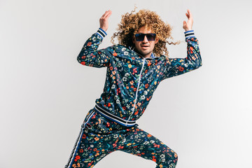 Obraz Excited adult funny man in stylish vintage clothes posing on white studio background. 80s fashion. Funky guy in tracksuit and sunglasses expressive indoor unusual portrait. Shouting cheerful male. - fototapety do salonu