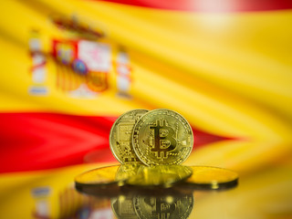 Bitcoin gold coin and defocused flag of Spain background. Virtual cryptocurrency concept.