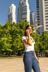 Portrait of a beautiful smiling young woman in a white shirt while talking on her phone on a sunny day.