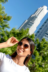 Portrait of a beautiful smiling young woman in a white shirt and sunglasses on a sunny day.