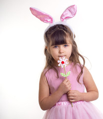 Little girl dressed as the Easter bunny standing on white background and holding flower. Child Easter Holiday Concept. Isolated.