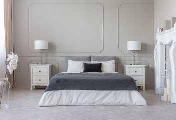 Grey blanket on white bedding on comfortable king size bed, two nightstand with lamps on both sides of it