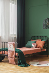 Dark orange and emerald green pillows on single metal bed in fashionable teenager's bedroom