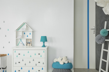 Blue lamp on white cabinet next to teddy bear on pouf in child's room interior. Real photo