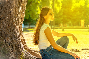 A beautiful young woman in a white shirt and sunglasses sitting next to a tree and enjoying the sunshine.
