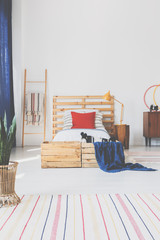 Real photo of an oldschool bedroom interior with wooden boxes, bed and striped rug
