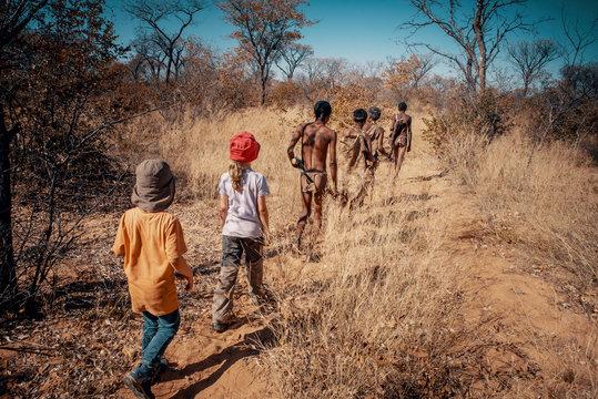 Kinder folgen einer Gruppe Buschmänner (Ju/'Hoansi-San) durch den Busch, Grashoek, Namibia