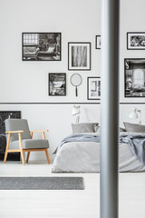 Wooden armchair next to bed in grey and white bedroom interior with gallery of photos. Real photo