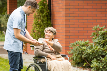 Male nurse giving tea to his senior patient in a wheelchair