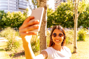 A beautiful young woman in a white shirt and sunglasses standing next to a tree and taking a selfie.