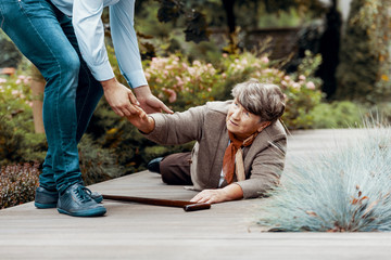Man helping female senior to get up from the ground