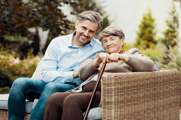Son and mother with a cane sitting on a wicker sofa in a garden