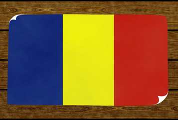 Illustration of a Romanian flag on the paper pasted on the woody wall