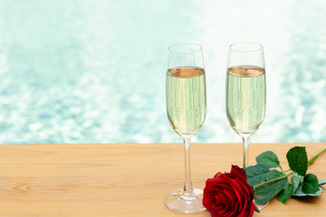 Two empty champagne glasses with rose flower next swimming pool.